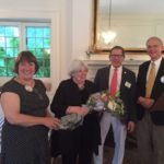 Bev Rogers (l) assisting Rainer Gonet (r) in presenting flowers to Carol Vazzana while Rich Vazzana looks on.